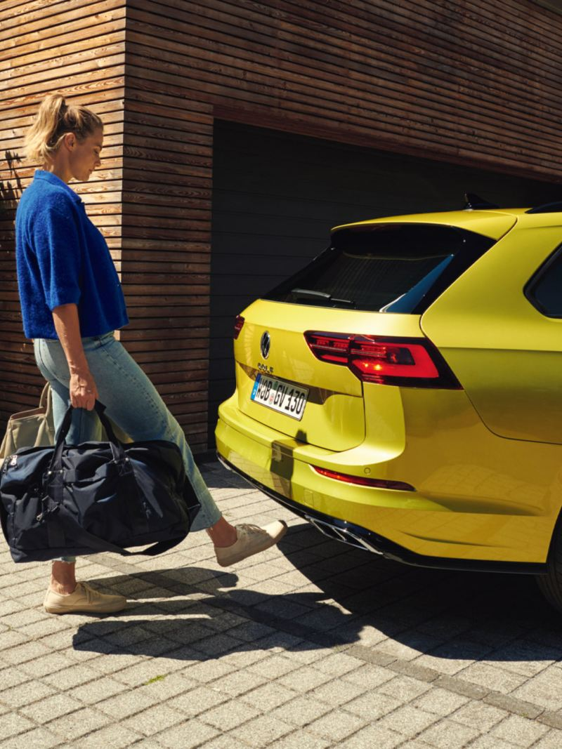 Woman opens the tailgate of the Golf Estate via Easy Open