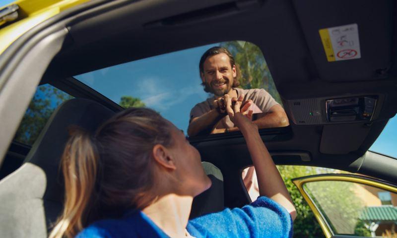 Mann und Frau schauen sich durch das Schiebedach des Golf Variant an.
