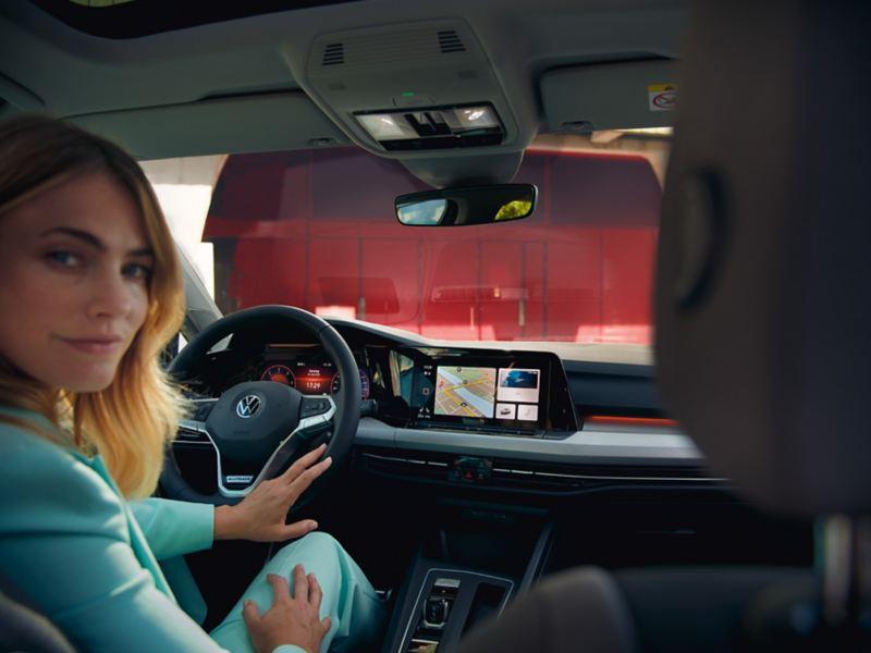 Blick vom Rücksitz auf das Cockpit des VWGolf Variant, auf dem Fahrersitz eine Frau im blauen Businessanzug.