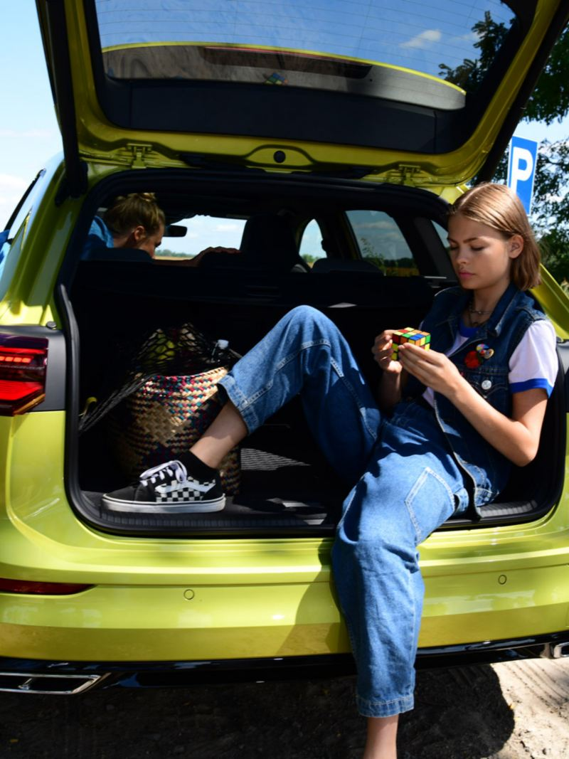 Girl sits in the open trunk of a Golf Variant