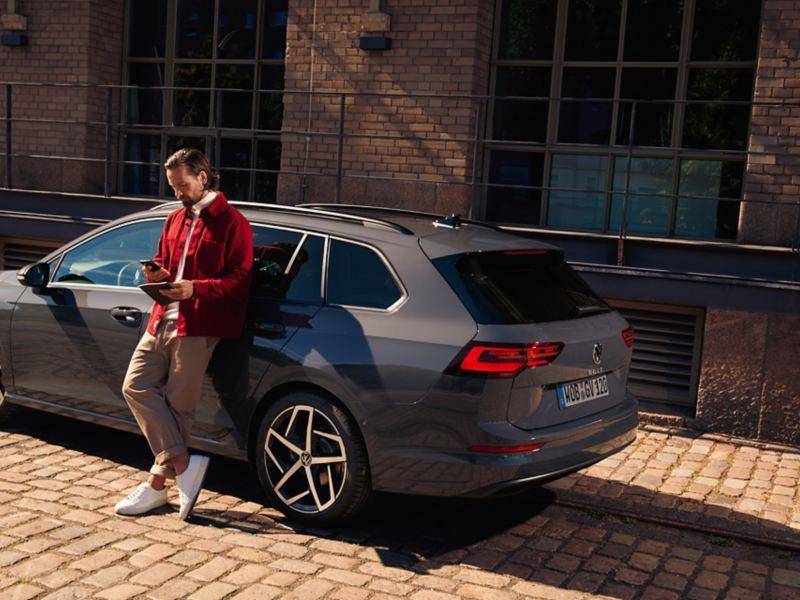 Ein Mann lehnt seitlich an einem grauen VW Golf Variant