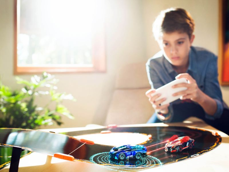 Bambino che gioca con Anki Overdrive in salotto