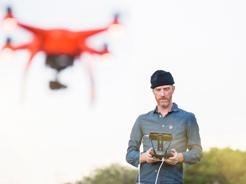 Mann fliegt ferngesteuerte Drohne im freien.
