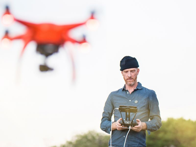 Uomo che fa volare un drone all'aperto comandandolo da lontano