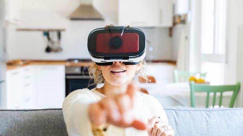 Donna con visore VR seduta sul divano di casa