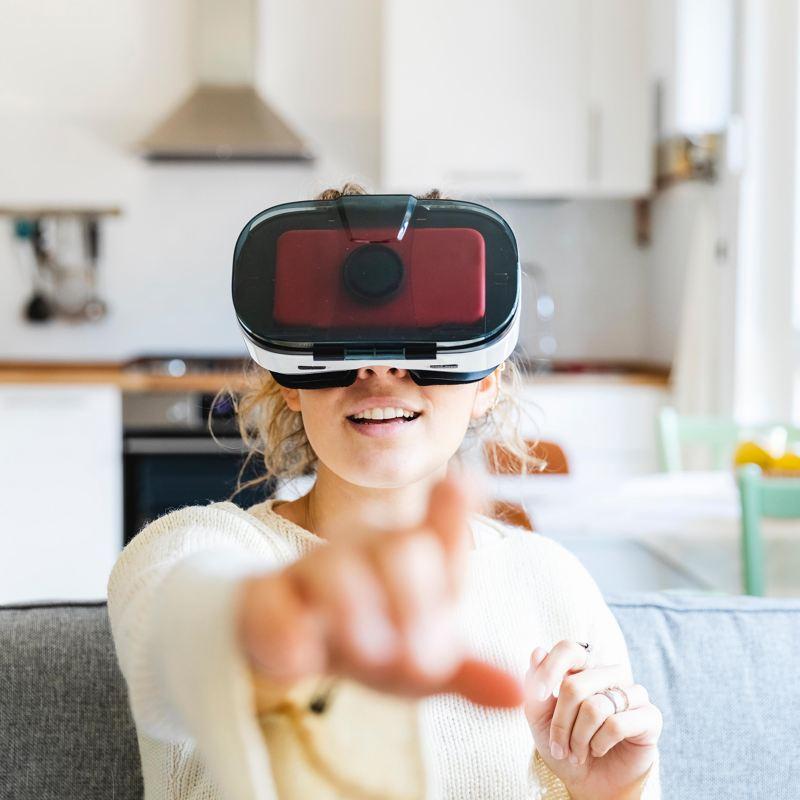 Frau mit VR-Brille sitzt Zuhause auf der Couch.