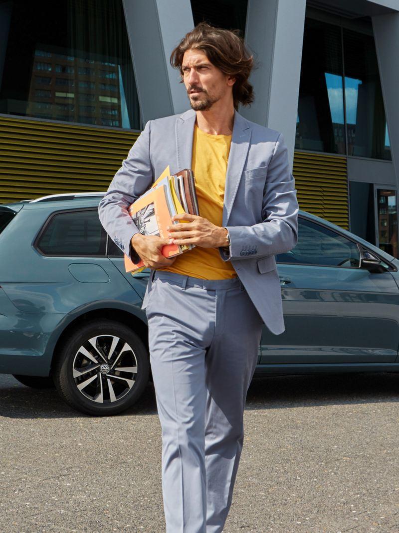 Uomo con giornali sottobraccio si allontana da Golf Variant VW con IQ Drive