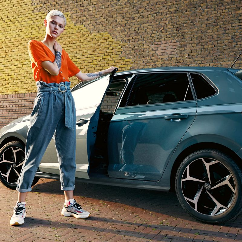 Ragazza a fianco di VW Nuova Polo IQ Drive con porta lato guida aperta