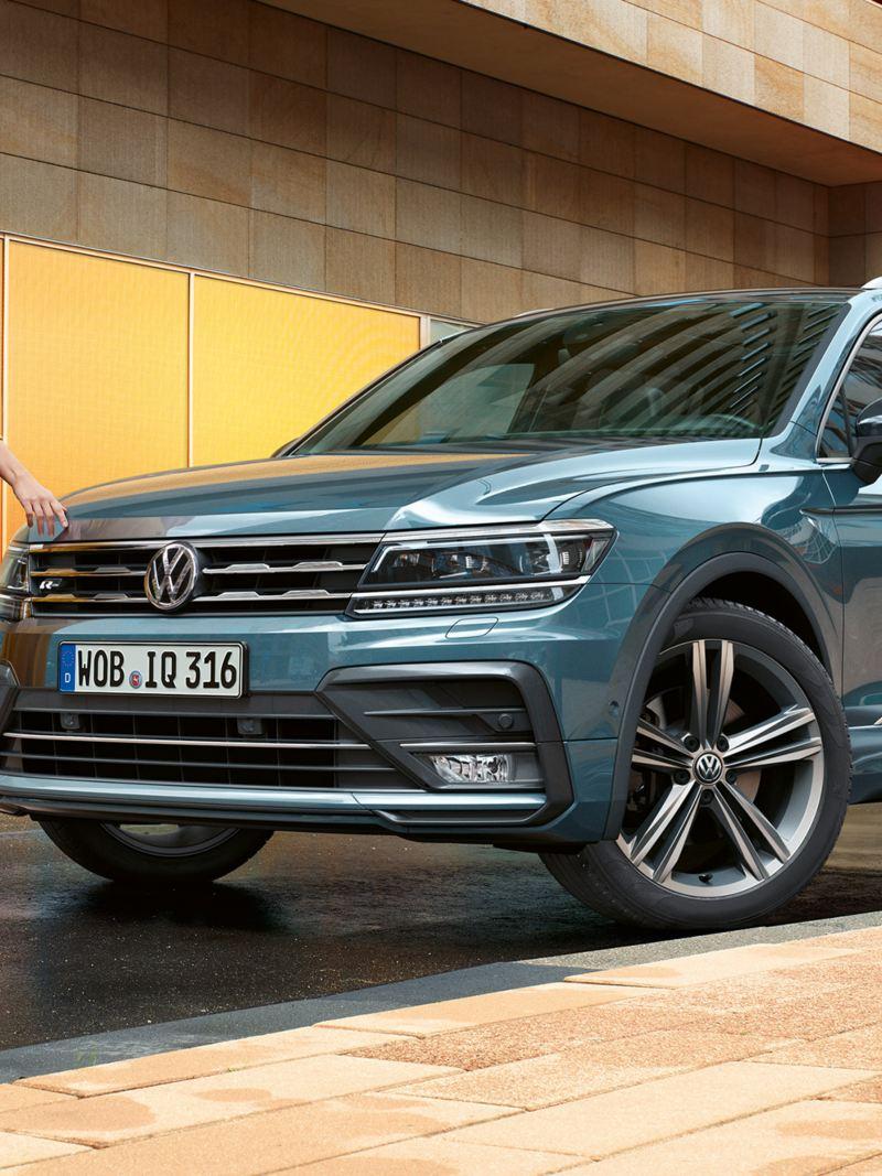 Donna si allontana da VW Tiguan Allspace IQ.Drive parcheggiata vicino a casa