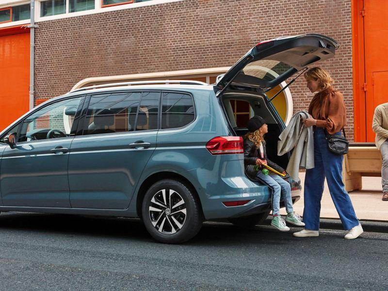 Mamma porge cappotto a ragazza seduta all'interno del bagagliaio aperto di VW Touran IQ.Drive