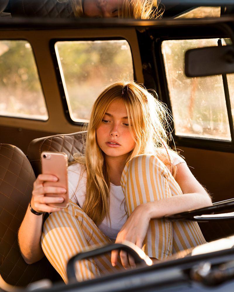 En ung kvinna sitter i en bil med blicken på sin mobiltelefon.
