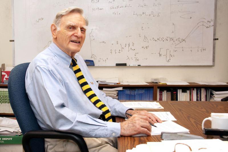 Der Erfinder des Lithium-Akkus sitzt an seinem Schreibtisch.