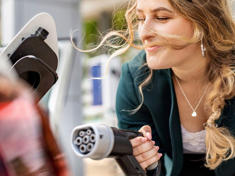 En kvinna håller en laddningskontakt till en elbil i handen.