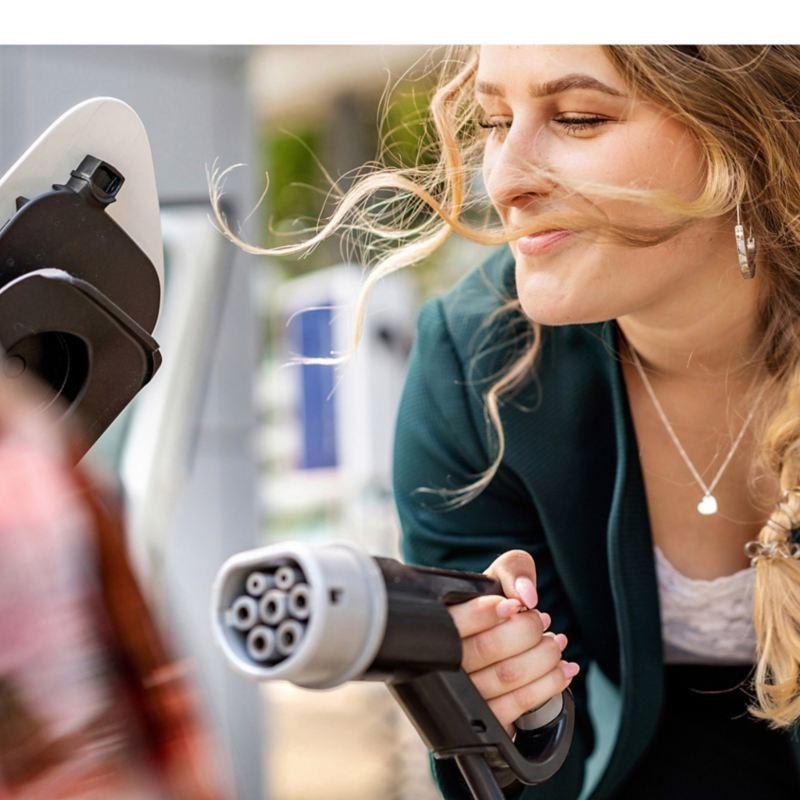 Donna che tiene in mano il connettore di ricarica per un'auto elettrica