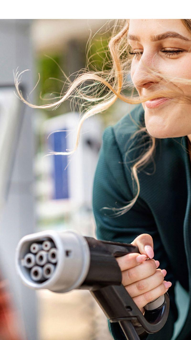 Primer plano de una mujer con el conector de un cargador eléctrico en la mano