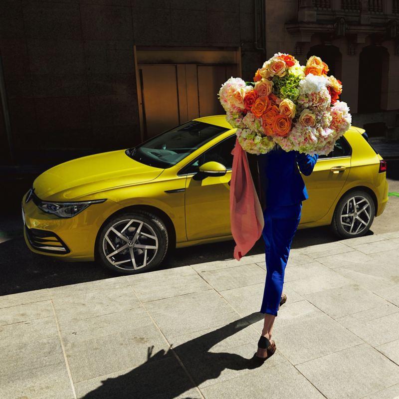 ragazza porta un enorme mazzo di fiori sulla spalle verso Volkswagen Golf 8 parcheggiata