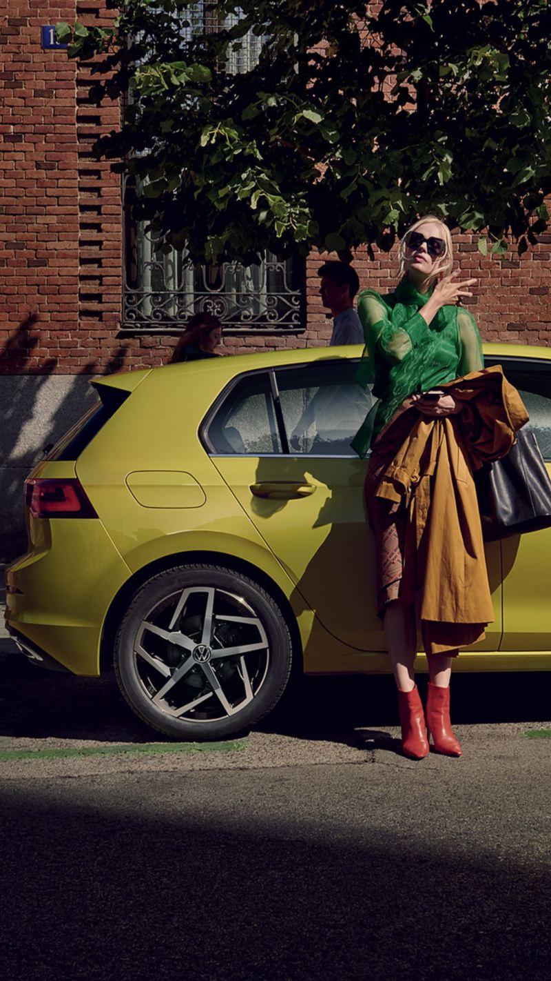 Ragazza appoggiata su Golf 8 Volkswagen parcheggiata