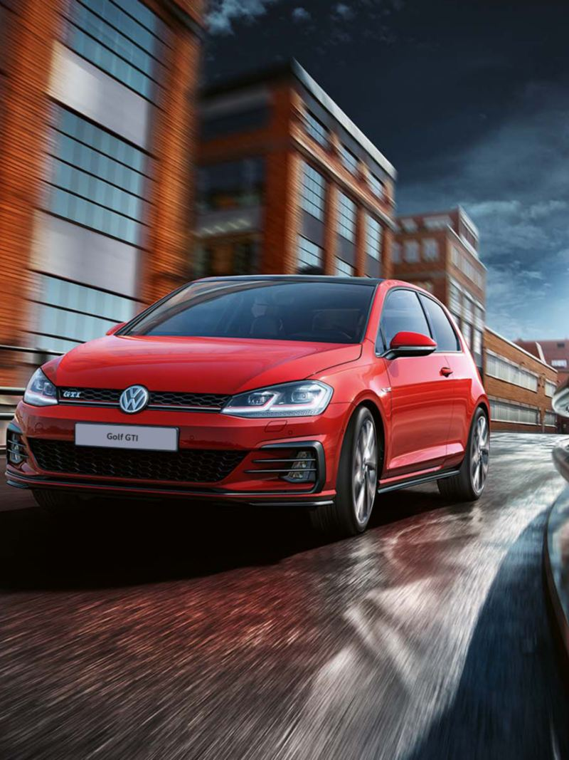 Red Volkswagen Golf GTI driving down highway in the city