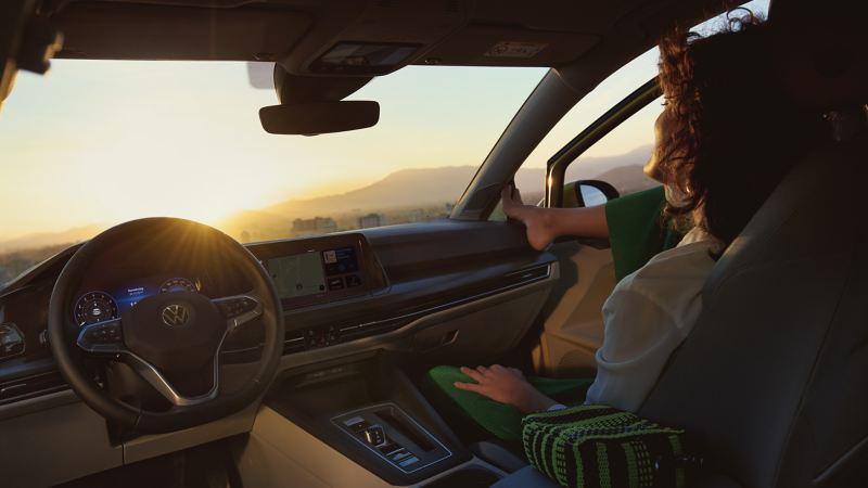 Kvinna sitter i passagerarsätet på en Volkswagen och tittar ut genom vindrutan ut mot solnedgången