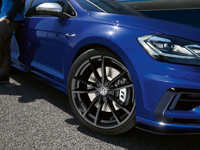Black optional alloy wheel on the Volkswagen Golf R MK7 painted in Lapis Blue Metallic parked on a racetrack