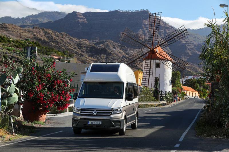 Grand California jedzie po uroczej uliczce - w tle wiatrak oraz góry
