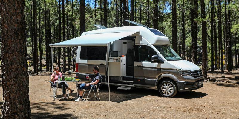 Para siedzi przy stoliku pod rozłożonym zadaszeniem Grand Californii, wokół las