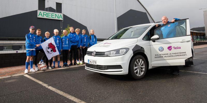 Kuva Volkswagen Touranista ja junioreiden jalkapallojoukkueen pelaajista auton vierellä