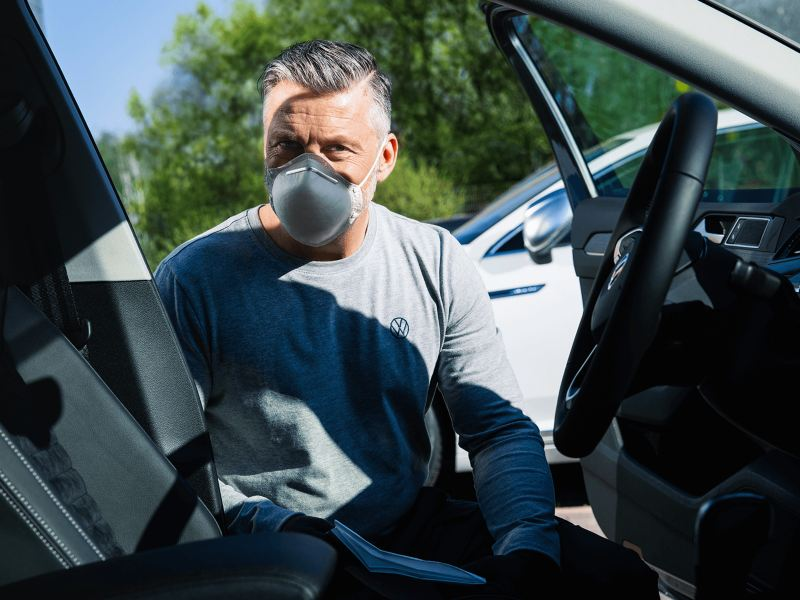 A man wearing a medical mask cleaning the inside of a car
