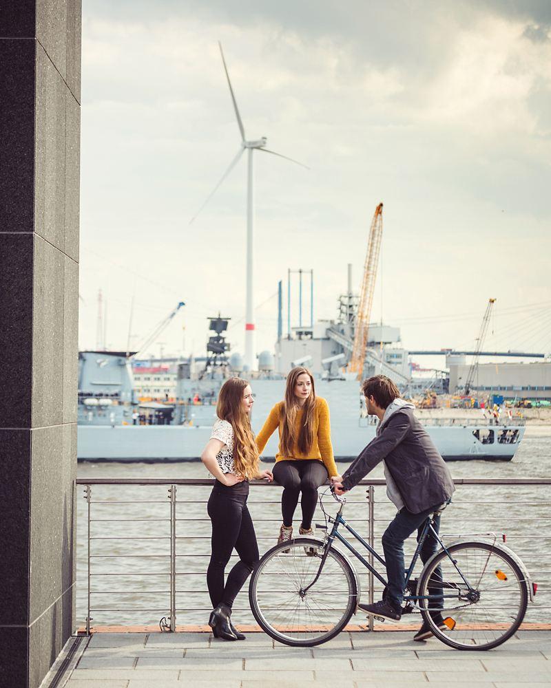 Zwei junge Frauen und ein junger Mann am Hamburger Hafen.