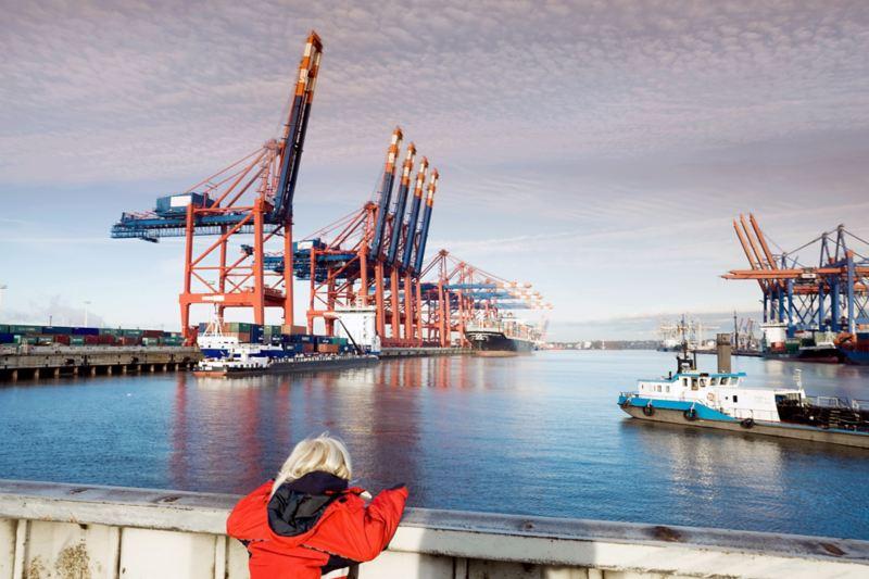 Ein rot gekleideter Mensch blickt auf die Schiffe im Hamburger Hafen.