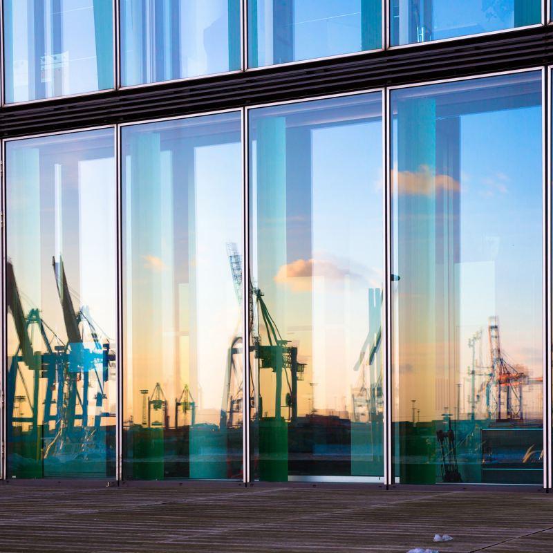 In der Glasfassade eines modernen Hauses spiegeln sich die Kräne des Hamburger Hafens.