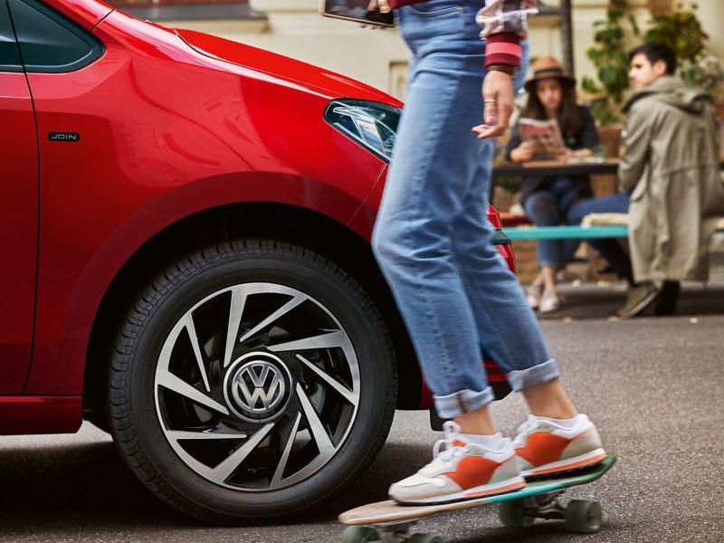 Une femme sur un skateboard pasae devnat une VW up rouge, la voiture est équipée de pneus été
