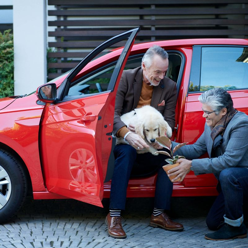 A man sat in a car and holding a dog