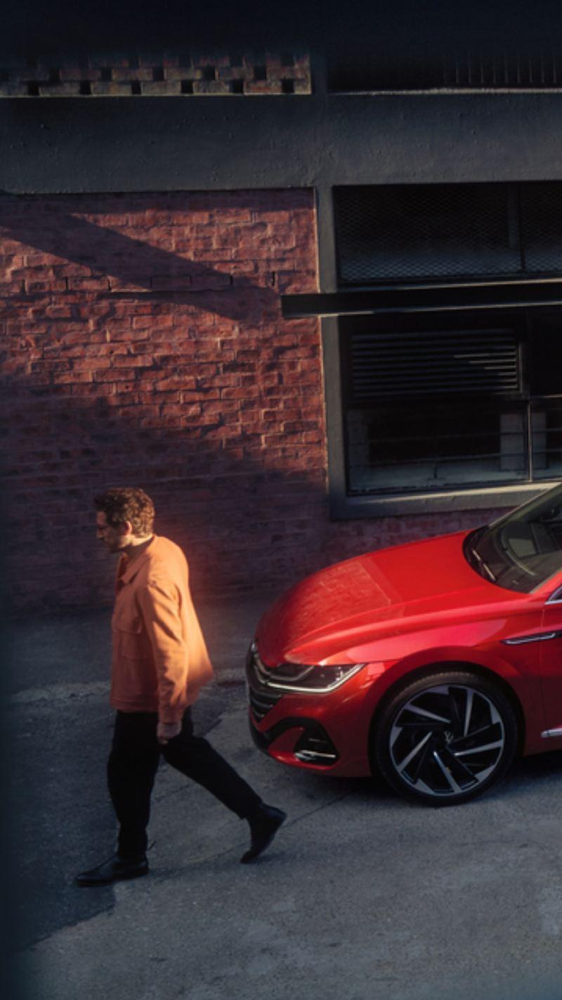 Vista lateral de un Nuevo Arteon Shooting Brake rojo tras un hombre avanzando por la calle