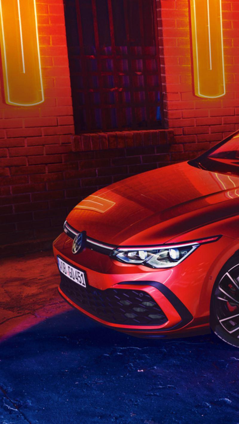 Volkswagen Golf 8 GTI rojo aparcado en la calle de noche iluminado por luces de neón