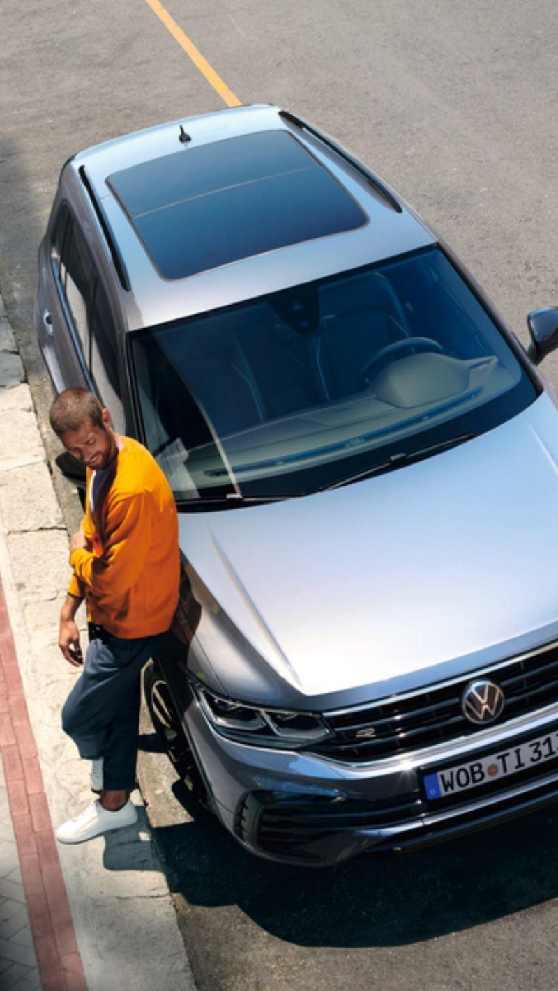 Vista superior de un hombre apoyado en un Volkswagen Nuevo Tiguan gris aparcado en la calle
