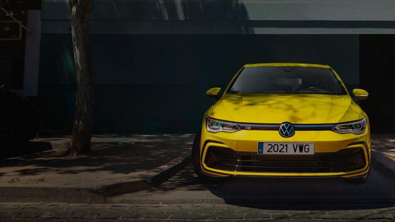 Volkswagen Golf 8 amarillo visto de frente aparcado bajo la sombra de un árbol