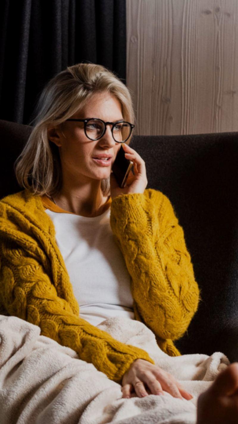 Mujer con un sueter amarillo hablando por teléfono sentada en el sofá de su casa