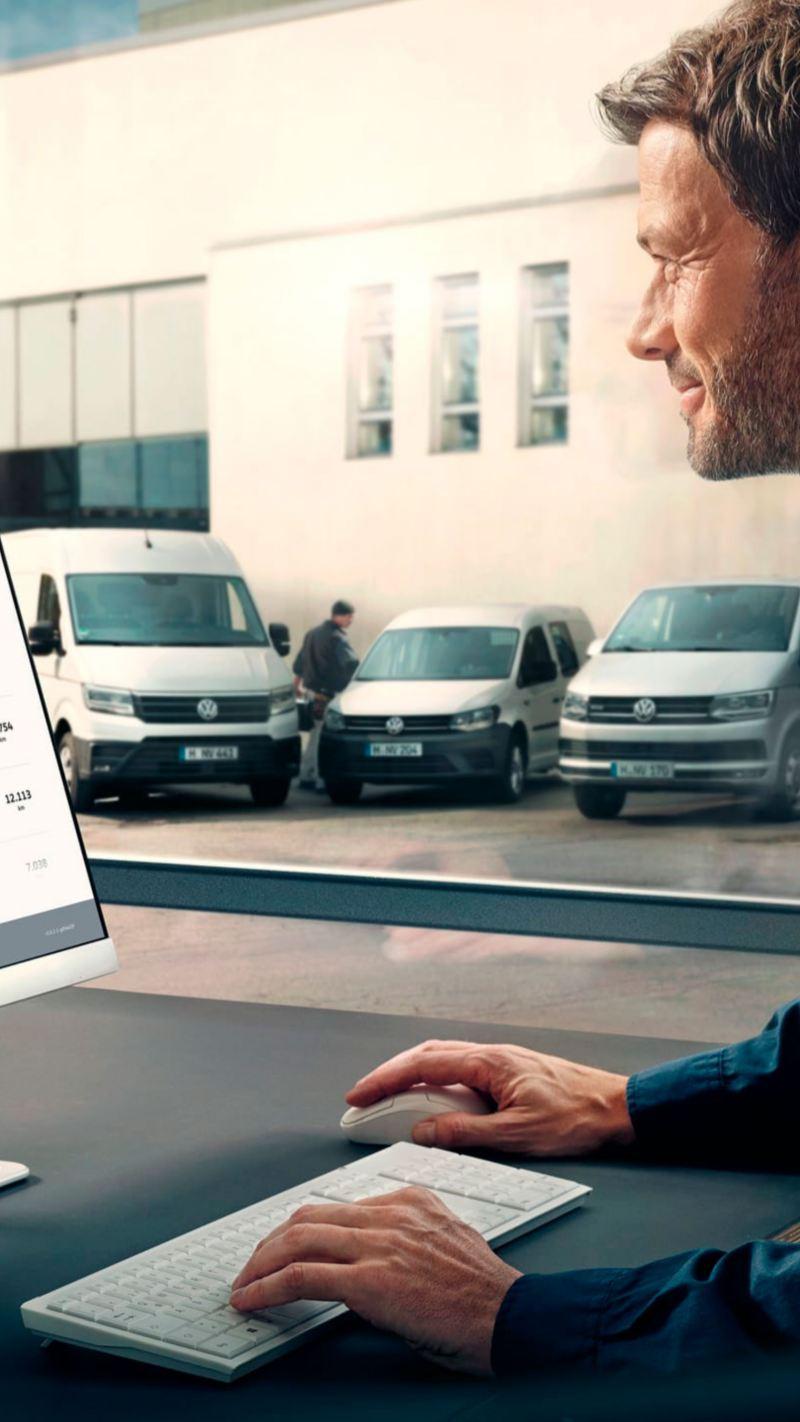 Homem sentado ao computador a ver carrinhas da Volkswagen Veículos Comerciais.