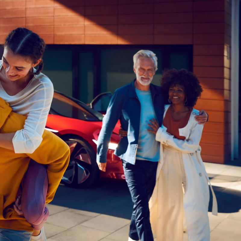 A family is in front of a Volkswagen electric car