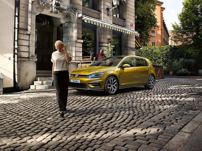 A yellow Volkswagen Golf R-Line parked on a cobbled street.