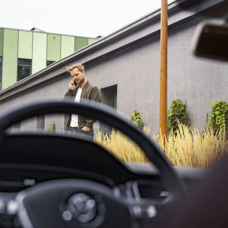 """Man in front of the VW car, link out to VW's """"warranties & coverage"""" page"""