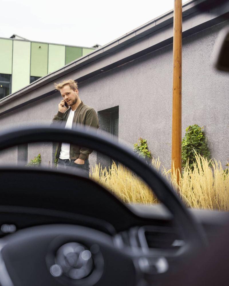 Homme devant la voiture VW, lien vers la page « Garanties et couverture » de VW