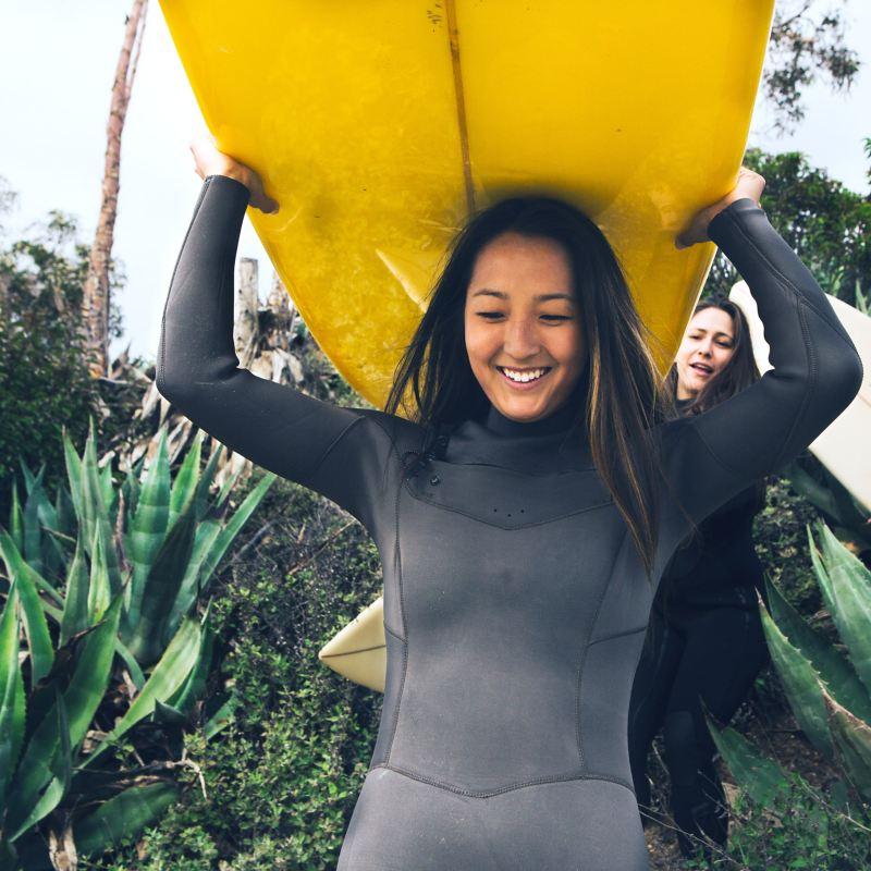 Junge Frau trägt Surfbrett über dem Kopf.