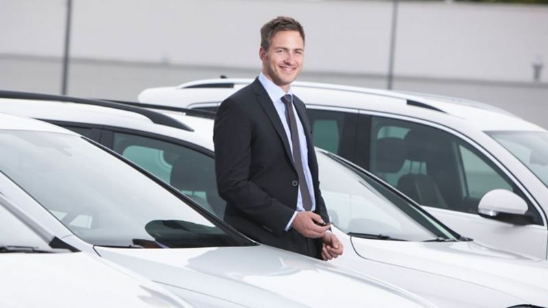 Un professionista insieme alle sue Volkswagen Business aziendali