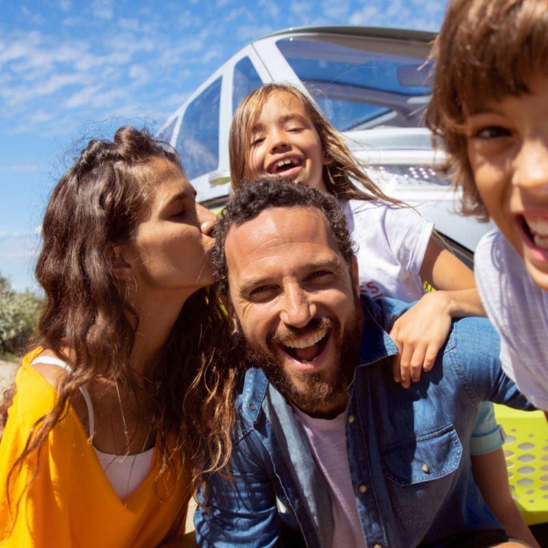 Kuva iloisesta perheestä, jossa kaikki hymyilevät ja nainen suukottaa miestä pään sivulle.
