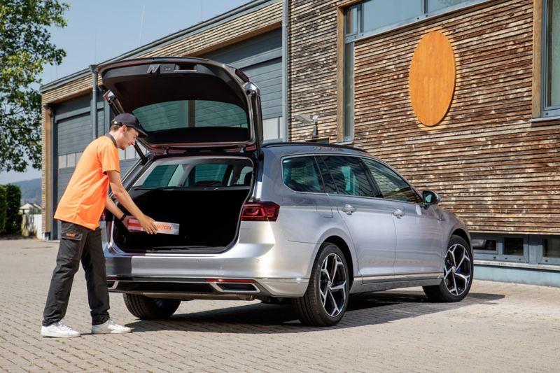 Un mensajero entrega un paquete en el maletero de un Volkswagen.
