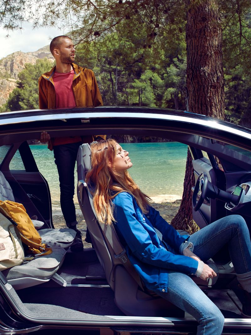 Mann und Frau entspannen mit ihrem Volkswagen am See