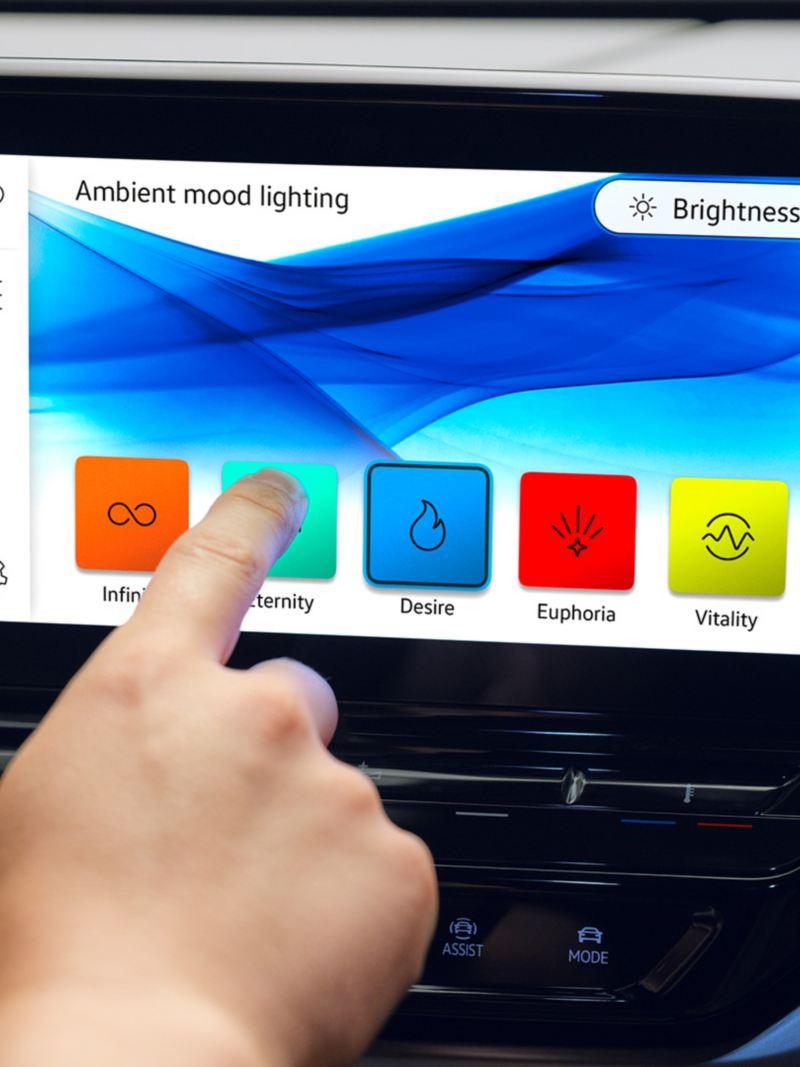 En mann endrer farger på ambientebelysningen i VW Volkswagen ID.4 elbil SUV