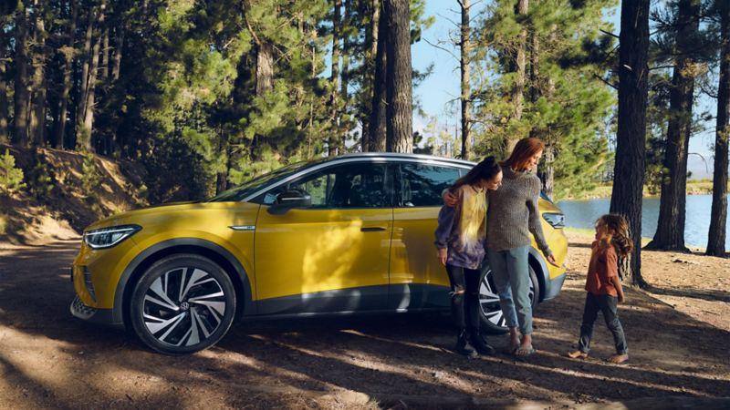 En familie står ved siden av VW Volkswagen ID.4 elbil SUV ved en innsjø